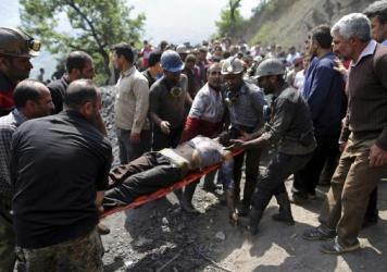 In this picture released by the Tasnim News Agency, miners and rescue personnel carry an injured mine worker after a coal mine explosion, near Azadshahr in northern Iran.  (AP Photo/Tasnim News Agency, Mostafa Hassanzadeh)