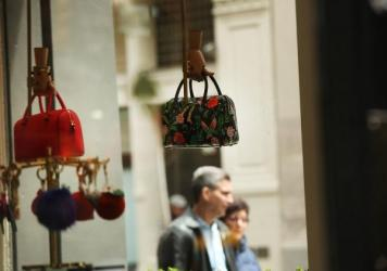 """Purses hang in the window of a Kate Spade store in New York City's SoHo neighborhood. The $2.4 billion deal with Coach aims to """"create the first New York-based house of modern luxury lifestyle brands."""""""