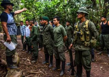 FARC guerrillas at a Colombia jungle camp last fall. Under last year's peace treaty, FARC agreed to disarm and confine its fighters to demobilization camps. But a small number of dissident rebels continue to extort business owners.