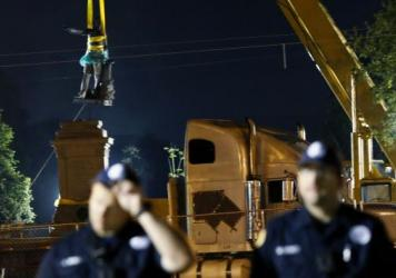 The statue of Jefferson Davis is removed from its base in New Orleans as police officers stand watch early Thursday. Demonstrators both for and against the removal of Confederate-era statues had gathered at the site.