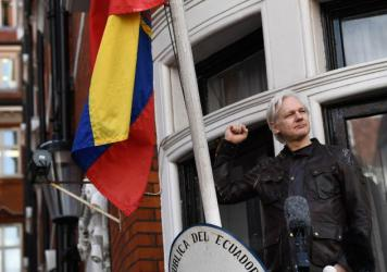 "WikiLeaks founder Julian Assange raises his fist before addressing reporters from the balcony of the Ecuadorian Embassy in London on Friday. In his speech, Assange said there are still plenty of legal battles still to wage: ""The proper war is just commen"