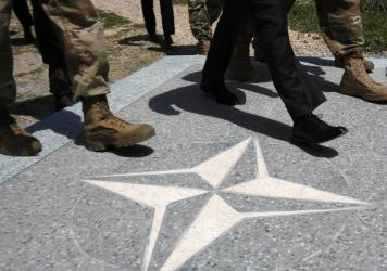 U.S. Defense Secretary James Mattis (in black dress shoes) walks with U.S. Army leaders across a NATO logo last month as he arrives at Resolute Support headquarters in Kabul, Afghanistan.