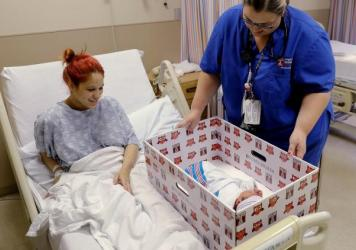 Keyshla Rivera smiles at her newborn son Jesus as registered nurse Christine Weick demonstrates a baby box before her discharge from Temple University Hospital in Philadelphia in 2016. All mothers who deliver at the hospital receive a box, which functions as a bassinet, in an effort to reduce unsafe sleep practices.