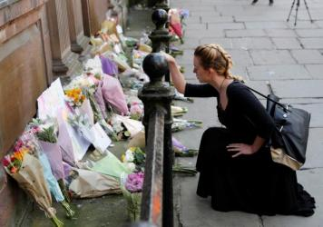 A woman lays flowers for the victims of the Manchester Arena attack in central Manchester on Tuesday.