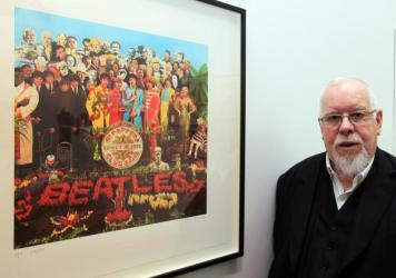 Pop artist Peter Blake poses beside a copy of the <em>Sgt. Pepper's Lonely Hearts Club Band </em>album cover, which he co-designed in 1967.