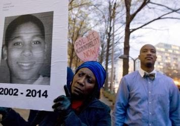 Tomiko Shine holds up a picture of Tamir Rice during a 2014 protest in Washington, D.C. Timothy Loehmann, the police officer who shot and killed the 12-year-old boy, was fired Tuesday for answers he provided on his personal history statement during the h