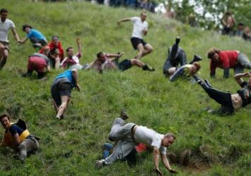 Competitors tumble down Coopers Hill in pursuit of a round Double Gloucester cheese during the 2016 cheese rolling competition near the village of Brockworth, Gloucester.