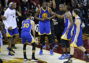 Golden State Warriors forward Kevin Durant, center, celebrates with teammates after the Warriors defeated the Cleveland Cavaliers 118-113 Wednesday night in Game 3 of the NBA Finals in Cleveland.