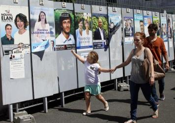 People in Bayonne, France, walk past posters for parliamentary elections, scheduled to take place June 11 and June 18.