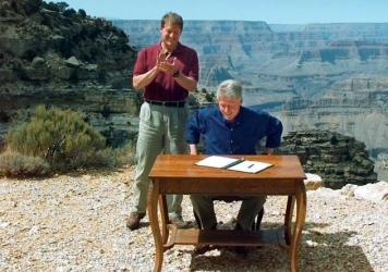 President Bill Clinton, with Vice President Al Gore, signs his 1996 order designating the Grand Staircase-Escalante National Monument in Utah. Opponents continue to note that Clinton made this move while sitting at the Grand Canyon — in Arizona.