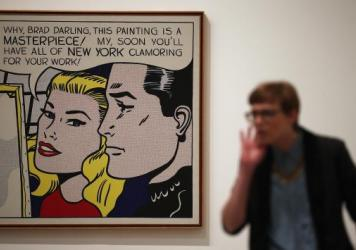 "A visitor stands in front of <em>Masterpiece</em> during a press preview of ""Lichtenstein, a Retrospective"" at the Tate Modern in London in 2013. The iconic painting was owned by Agnes Gund, who recently sold it to fund a new criminal justice reform fund."