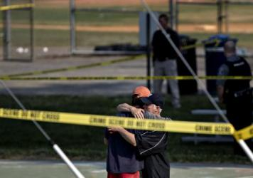 Two people embrace near the blocked-off crime scene in Alexandria, Va., where a congressman and several others were wounded in a shooting during a congressional baseball practice Wednesday. The suspected gunman has died, officials say.