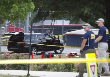 An SUV, with a bullet hole in the windshield and a flat tire, sits in the parking lot at the baseball field where Rep. Steve Scalise was shot Wednesday morning.