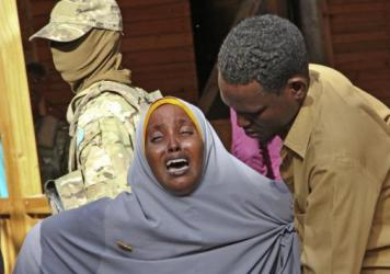 A woman grieves for her daughter, who was shot by militants during an attack on a restaurant in Mogadishu, Somalia. Early Thursday, Somali security forces ended a nightlong siege by al-Shabab extremists at the popular Pizza House restaurant in the countr
