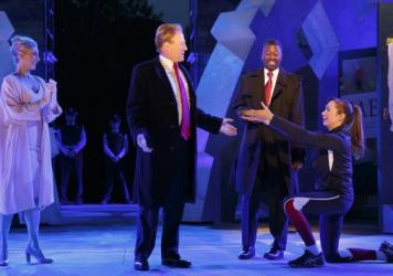 In this May 21, 2017, photo provided by The Public Theater, Tina Benko, left, portrays Melania Trump in the role of Caesar's wife, Calpurnia, and Gregg Henry, center left, portrays President Donald Trump in the role of Julius Caesar during a dress rehearsal of The Public Theater's Free Shakespeare in the Park production of <em>Julius Caesar</em> in New York.