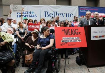 Doctors, nurses, patients and activists listen to Senate Minority Leader Chuck Schumer, D-N.Y., speak about Senate Republicans' health care bill on Friday at Bellevue Hospital in New York City. Schumer has vowed to help defeat the legislation, which the