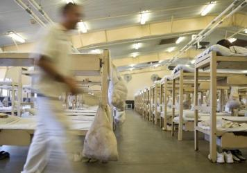 In this June 18, 2015, photo, a prisoner walks near his crowded living area in Elmore Correctional Facility in Elmore, Ala. Tuesday's ruling comes in a class action lawsuit brought by inmates who argued the conditions violated the U.S. Constitution's ban