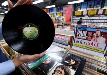 A store manager shows off a Japanese pressing of The Beatles' <em>Let It Be</em> at the RECOfan music shop in Tokyo's Shibuya district. Demand for vinyl records is leading Sony to restart making vinyl records.