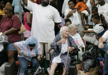 Hurricane Katrina victims wait at the Convention Center in New Orleans, in September 2005. A report from <em>Scientific American</em> says such natural disasters may increase the gap between rich and poor in affected communities.