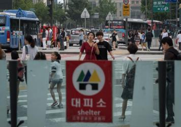 A shelter sign is displayed at the entrance to a subway station in Seoul on Wednesday, a day after North Korea tested an intercontinental ballistic missile. Subway stations are designated as shelters in case of aerial bombardment, part of the city's response to the threat posed by North Korea. But many Seoul residents take the threat in stride.