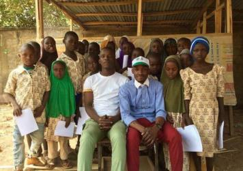 Aweofeso Adebola (in white shirt) and Ifeoluwa Ayomide (in cap) pose with some of their students. Zachariah Ibrahim, who dreams of being a pilot, stands behind the girl in the green hijab. Fatima Alidarunge, who wants to be a soldier to fight Boko Haram,