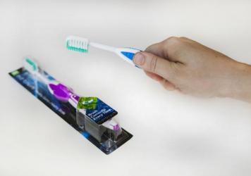 The MD Brush toothbrush forces users to hold it at the optimal angle relative to their gums.