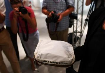 During a media preview on July 13, Cassandra Hatton of Sotheby's displays the Apollo 11 contingency lunar sample return bag. It was used by Neil Armstrong on Apollo 11 to bring back the first pieces of the moon ever collected.