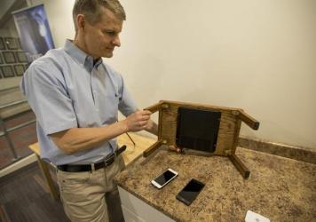 Morris Kesler, chief technology officer at WiTricity, shows how a wireless charging pad can be installed on a table.