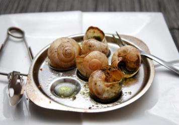 Employees at Croque Bourgogne put the cooked flesh of Burgundy snails into shells before being packaged and shipped to grocery stores in France. The company imports the snails from Hungary.