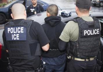 """In this February photo released by U.S. Immigration and Customs Enforcement, agents arrest foreign nationals. According to a Massachusetts Supreme Judicial Court ruling Monday, local law enforcement cannot honor ICE """"detainers,"""" which request that a pers"""