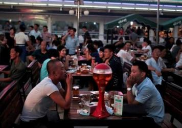 "North Koreans enjoy beer and snacks last August during the Taedonggang Beer Festival in Pyongyang. The festival, the first of its kind in the country, was held as a promotional event for the locally brewed beer. Korean signs in the background read ""Our country is the best."""