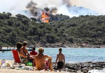 One of France's massive forest fires is visible from the beach in La Croix-Valmer, near Saint-Tropez. Thousands of French firefighters have been battling blazes that consumed swaths of land in southeastern France.