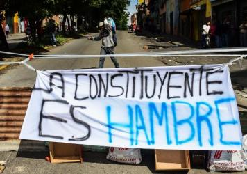 "Venezuelans began blocking  deserted streets Wednesday as the opposition held a two-day strike opposing President Nicolas Maduro's planned vote for a new Constituent Assembly. A banner reading ""The Constituent Is Hunger,"" is seen in Caracas' Petare neigh"