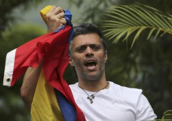 In a photo taken lasy month, Venezuela's opposition leader Leopoldo Lopez holds a national flag as he greets supporters outside his home in Caracas, Venezuela, following his release from prison and being placed under house arrest after more than three years in military lockup.