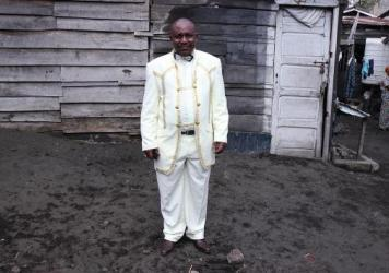 "Theobold Kawa, a 55-year-old pastor, stands outside of AEPL Makedonia church in Goma. He  bought his suit in Uganda. ""I'm dressing up like this because of the Glory of God,"" he says. ""A servant of God shouldn't look dirty."""
