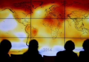 Participants look at a world map showing climate anomalies during the World Climate Change Conference 2015 in France. A draft government report on climate, which was leaked ahead of publication, says the U.S. is already experiencing the consequences of g