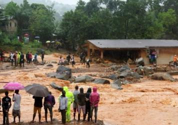Bystanders look on as floodwaters rage past a damaged building on the outskirts of Freetown on Monday, after mudslides struck near the capital of the west African state of Sierra Leone.