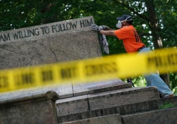 "Baltimore city workers remove graffiti from the pedestal where a statue dedicated to Robert E. Lee and Thomas ""Stonewall"" Jackson stood on Wednesday. The City of Baltimore removed four statues celebrating confederate heroes from city parks overnight, following the weekend's violence in Charlottesville, Va."