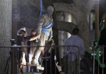 A statue of Confederate Gen. Robert E. Lee is removed from the University of Texas campus, early Monday morning in Austin.