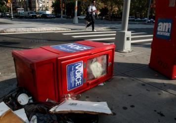 A<em> Village Voice</em> newspaper stand lays on the ground next to garbage in New York City's East Village on Tuesday. <em>The</em> <em>Village Voice</em>, one of the oldest and best-known alternative weeklies in the U.S., announced that it will no long