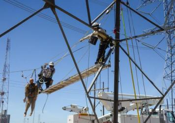 "Utility workers use an APA-5 Atlas Powered Ascender to practice a pick-off operation, quickly rescuing a lineman who had ""fallen"" from his position on a high voltage transmission line."