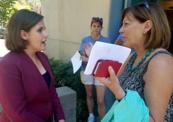 Democratic congressional candidate Regina Bateson (left) speaks with local resident Paige Stauss outside a public library in Granite Bay, Calif., following a campaign event.