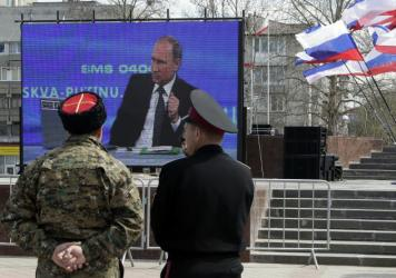 Cossacks look at Russian President Vladimir Putin answering a question on television, in Simferopol, Crimea in 2015.