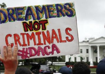 A woman holds up a sign in support of the Obama administration program known as Deferred Action for Childhood Arrivals, or DACA, during a rally at the White House on Aug. 15.