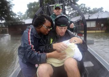 Shardea Harrison looks at her 3-week-old baby, Sarai Harrison, being held by Dean Mize as he and Jason Legnon used an airboat to rescue them Monday from their home in Houston after the area was inundated by Tropical Storm Harvey.