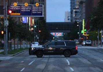A police car patrols in downtown Houston on Wednesday following the first night of curfew after Harvey caused heavy flooding in the city.