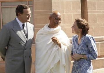 Lord Louis Mountbatten (Hugh Bonneville), Mahatma Gandhi (Neeraj Kabi) and Lady Edwina Mountbatten (Gillian Anderson) smile politely in <em>The Viceroy's House</em>.