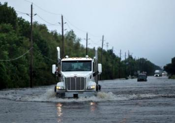 Trucks make their way through floodwaters on a road leading to Arkema Inc. in Crosby, Texas, Wednesday. Chemicals at the plant are in danger of exploding because refrigeration is out owing to Hurricane Harvey.
