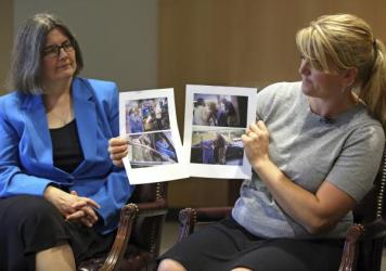 Nurse Alex Wubbels (right) displays video frame grabs of herself being taken into custody while her attorney, Karra Porter, looks on during an interview Friday. Wubbels was arrested after she told a police detective it was against hospital policy to cond