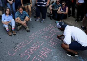 Hundreds of people gather for a vigil on the spot where 32-year-old Heather Heyer was killed when a car plowed into a crowd of people protesting against the white supremacist Unite the Right rally August 13, 2017 in Charlottesville, Virginia.